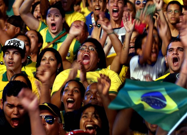 Fans celebrate after Brazil scores a goal against Croatia, at a Fan Fest complex in Recife, Brazil. (Photo by Dolores Ochoa/Associated Press)