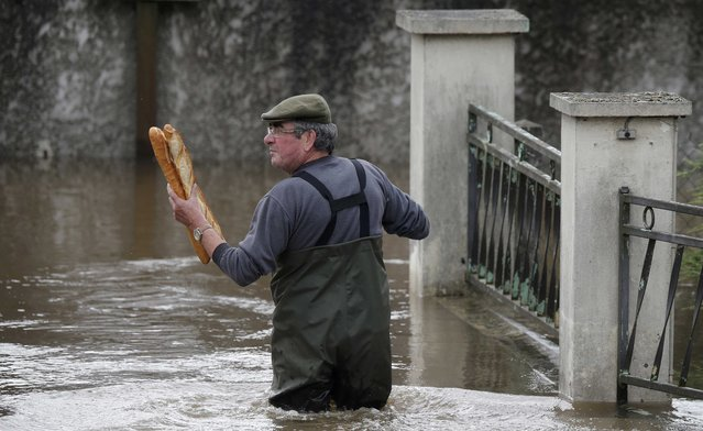 A resident brings French baguettes to his mother's flooded house after heavy rain falls in Chalette-sur-Loing Montargis, near Orleans, France, June 1, 2016. (Photo by Christian Hartmann/Reuters)