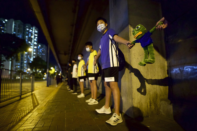 Protesters join hands with a cartoon frog doll as they form a human chain during a rally in Hong Kong, Saturday, November 30, 2019. (Photo by Ng Han Guan/AP Photo)