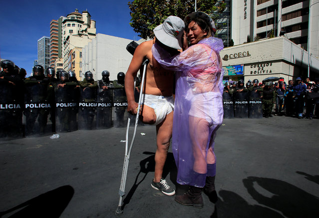 Demonstrators with a physical disability stand in front a riot police barricade during a protest calling on the government to provide a monthly subsidy for the physically disabled rather than an annual one, in El Alto, Bolivia, June 3, 2016. (Photo by David Mercado/Reuters)