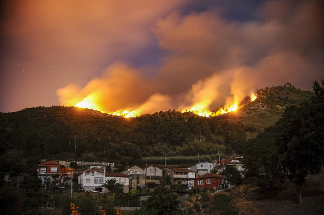 View of Untes village surrounded by the flames of a forest fire which is avanced to be declared risk level two because it has surrounded houses, it has affected a farm and two firefighting team members have been evacuated near Ourense, Galicia, northwestern Spain, 28 July 2015. (Photo by Brais Lorenzo/EPA)