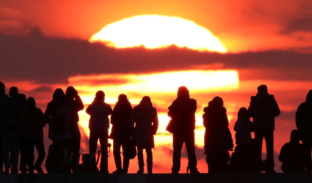 People watch the first sunrise on New Year's Day at Yuriage district where an area was damaged by the March 11, 2011 earthquake and tsunami, in Natori, Miyagi prefecture, Japan, in this photo taken by Kyodo January 1, 2017. (Photo by Reuters/Kyodo News)