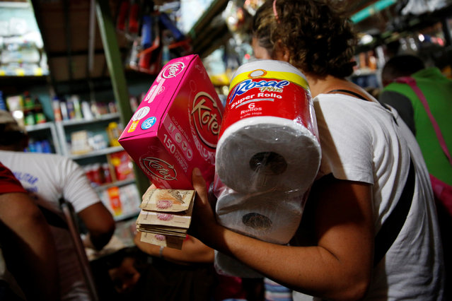 A woman holding Venezuelan bolivar notes carries a pack of toilet paper at a store in Puerto Santander, Colombia, June 3, 2016. (Photo by Carlos Garcia Rawlins/Reuters)