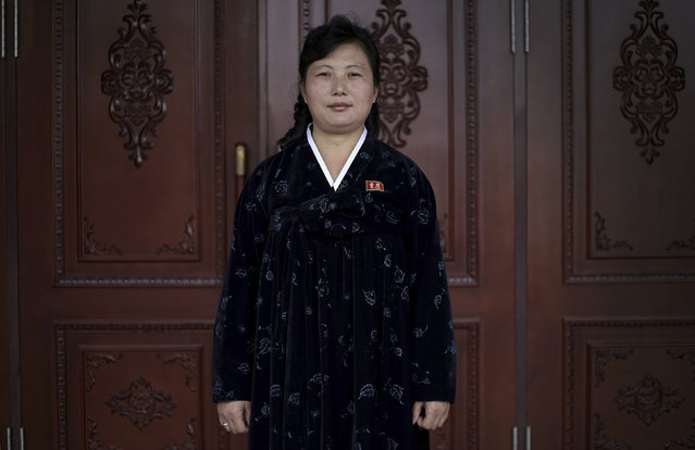 """In this April 10, 2017, photo, Kim Son Hui, 41, stands at the entrance of the Pyongyang Class Education Hall as she poses for a portrait in Pyongyang, North Korea. Kim has been working as a guide for the past 15 years. Her motto: """"I want to make other people dedicated to the building of a thriving nation by giving lectures and tours, as a guide, for as long as I can"""". (Photo by Wong Maye-E/AP Photo)"""
