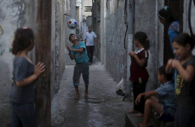 A Palestinian boy plays football outside his family house at Shatti (beach) refugee camp in Gaza City July 28, 2015. (Photo by Mohammed Salem/Reuters)
