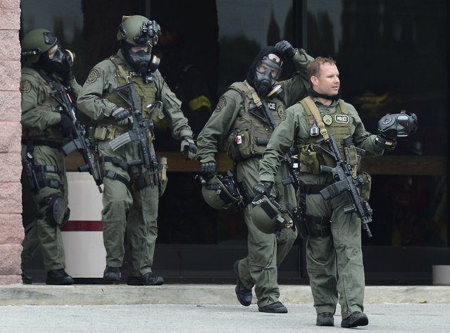 Nashville Metro Police officers exit the movie theater  following a shooting Wednesday, August 5, 2015, in Antioch, Tenn. A man armed with a hatchet and a pellet gun unleashed a volley of pepper spray at audience members inside a movie theater, exchanging fire with a responding officer before being shot dead as he tried to escape out the back of the theater only to encounter a SWAT team, police said. (Photo by Mark Zaleski/AP Photo)