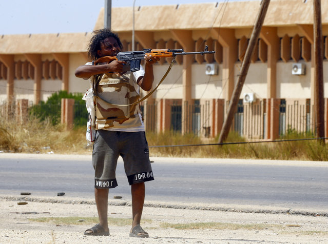 A fighter loyal to the UN-recognised Government of National Accord (GNA) points his gun toward enemy lines during clashes with forces loyal to strongman Khalifa Haftar, in Espiaa, about 40 kilometers (25 miles) south of the Libyan capital Tripoli on August 21, 2019. (Photo by Mahmud Turkia/AFP Photo)