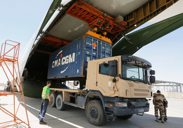 French crew members unload containers from a plane that landed in Baghdad, carrying weapons to the Iraqi government to help in its fight against Islamic State militants in Baghdad, Iraq June 17, 2016. (Photo by Ahmed Saad/Reuters)
