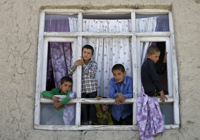 Children look out from the broken window of a house near the site of a car bomb blast at the entrance gate to Kabul airport, Afghanistan August 10, 2015. (Photo by Mohammad Ismail/Reuters)