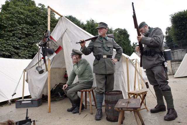 Men dressed in Austro-Hungarian World War I military uniforms stand outside a tent at a WWI military camp reconstitution in the Tuilleries Garden in Paris on July 13, 2014, on the eve of Bastille Day, France's National Day. (Photo by Thomas Samson/AFP Photo)