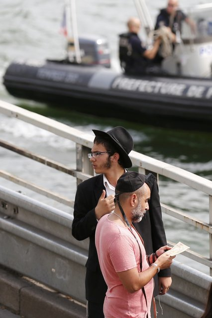 """French police patrol on the River Seine as Jewish men are seen at """"Paris Plages"""" during the """"Tel Aviv on Seine"""" event in Paris, France, August 13, 2015. (Photo by Pascal Rossignol/Reuters)"""