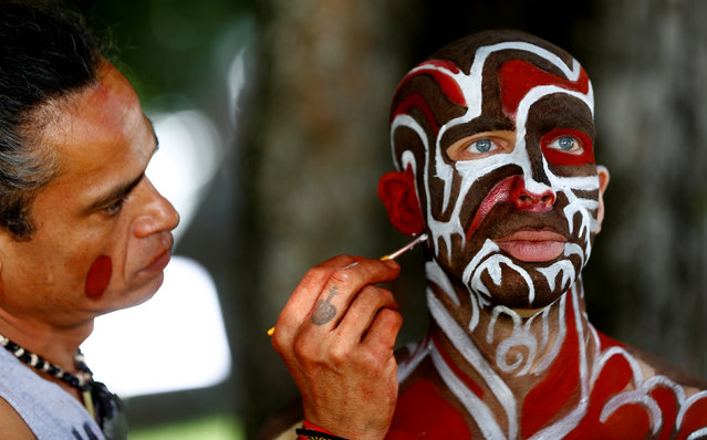 """An artist touches up makeup on a model during the """"World Bodypainting Festival 2017"""" in Klagenfurt, Austria on July 28, 2017. (Photo by Leonhard Foeger/Reuters)"""