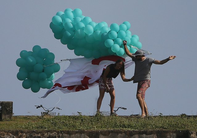 A tourist couple gets entangled in balloons during a United National People's party election campaign rally in Galle August 14, 2015. (Photo by Dinuka Liyanawatte/Reuters)