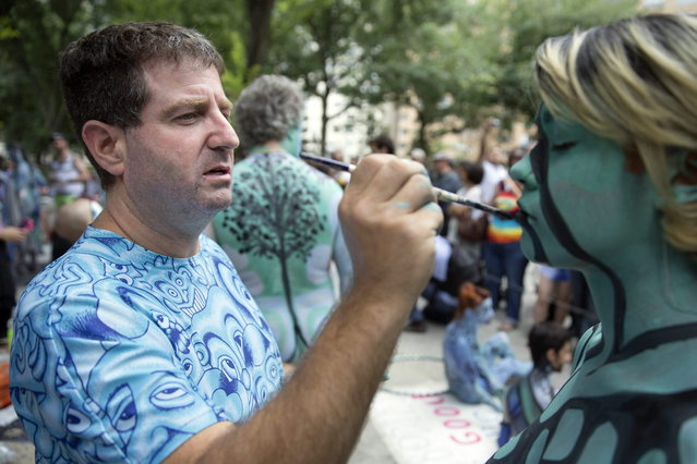 Artist Andy Golub paints a model at Columbus Circle as body-painting artists gathered to decorate nude models as part of an event lead by Golub, Saturday, July 26, 2014, in New York. Golub says New York was the only city in the country that would allow his inaugural Bodypainting Day. (Photo by John Minchillo/AP Photo)