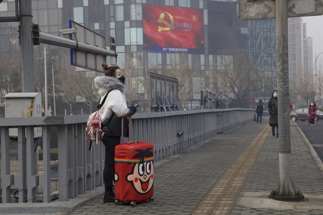 A traveler stands on a bridge near a display showing government propaganda in the fight against the COVID-19 viral illness in Beijing, China Thursday, February 13, 2020. (Photo by Ng Han Guan/AP Photo)