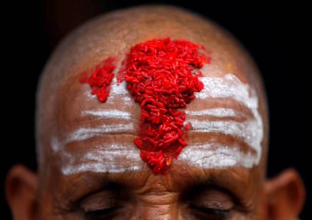 """A Hindu priest's forehead is covered with """"tika"""", coloured powder and rice used as a blessing, during the sacred thread festival at the Pashupatinath temple in Kathmandu, Nepal July 28, 2017. Hindus take holy baths and change their sacred threads, also known as janai, for protection and purification during the festival. (Photo by Navesh Chitrakar/Reuters)"""