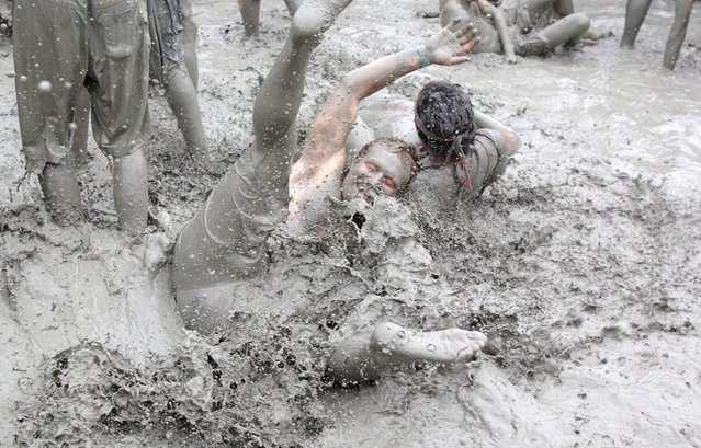 Festival goers plays in mud during the 15th Annual Boryeong Mud Festival at Daecheon beach in Boryeong, southwest of Seoul