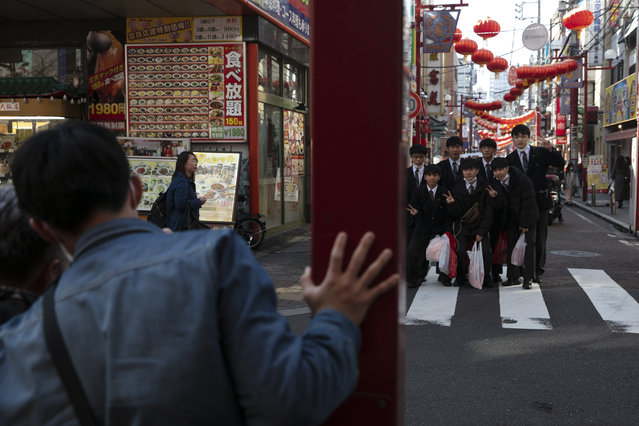 In this February 13, 2020, photo, a group of students gather for a group picture in Yokohama's Chinatown, near Tokyo. A top Olympic official made clear Friday the 2020 Games in Tokyo will not be cancelled despite the virus that has spread from China. (Photo by Jae C. Hong/AP Photo)