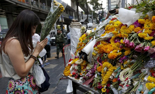 A woman places a bouquet of flowers at the Erawan shrine, the site of Monday's deadly blast, in central Bangkok, Thailand, August 20, 2015. (Photo by Chaiwat Subprasom/Reuters)