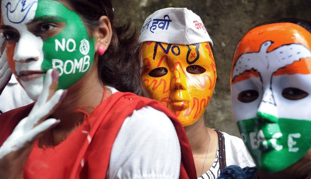 Indian youth activists wear masks carrying slogans for peace as they take part in a rally to mark Hiroshima Day in Mumbai on August 6, 2014. Peace rallies and memorial services the world over marked the world's first nuclear attack on Hiroshima – the moment in 1945 when a single US bomb instantly killed more than 140,000 people and fatally injured tens of thousands of others with radiation or horrific burns. (Photo by Indranil Mukherjee/AFP Photo)