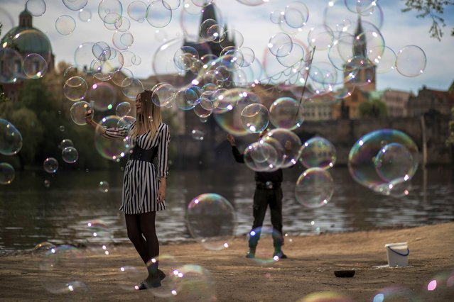 A woman takes a selfie photo as a man blows bubbles on the Vltava river bank in Prague, Czech Republic, 26 April 2019. (Photo by Martin Divisek/EPA/EFE)