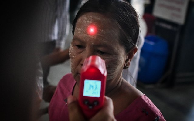 A woman wearing traditional face cosmetic has her temperature taken as a preventive measure against the COVID-19 coronavirus at the central railway station in Yangon on March 19, 2020. (Photo by Ye Aung Thu/AFP Photo)