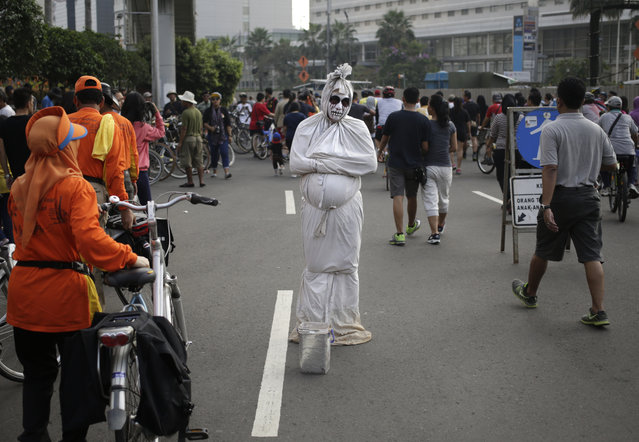 "A man dressed as a shrouded ghost locally known as a ""pocong"" busks for small money during a car free day in the main business district in Jakarta, Indonesia, Sunday, July 17, 2016. (Photo by Dita Alangkara/AP Photo)"