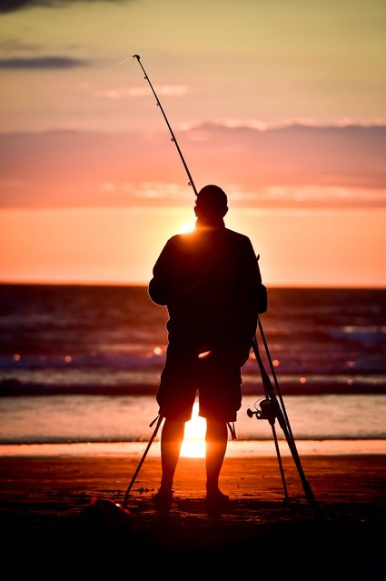A fishermen makes the most of the daylight as he casts into the sea at Woolacombe beach, North Devon, as the sun sets after another hot day in the South West UK, on July, 29, 2014. (Photo by Ben Birchall/PA Wire)