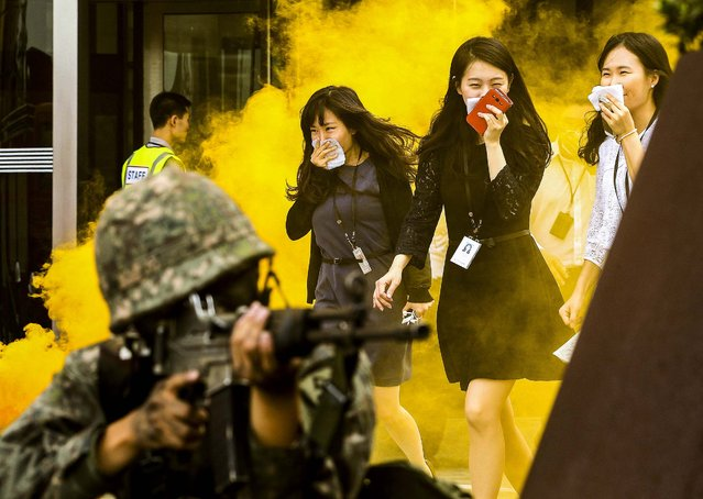 People evacuate from a building during a civil defense drill against possible attacks by North Korea, as part of the annual Ulchi Freedom Guardian exercise in Seoul, South Korea, on August 20, 2014. (Photo by Ahn Young-joon/Associated Press)