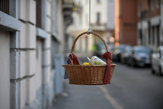 "One of the baskets with food and other goods hanging from balconies and left at disposition of people in need during the coronavirus emergency in Milan, Italy, Saturday, April 4, 2020. The initiative, dubbed ""hanging baskets"", was born after an old Neapolitan tradition, that of the ""hanging coffee"" (Caffe' sospeso) that customers pay in bars and are left at disposition of whoever enters the bar and asks for it. (Photo by Claudio Furlan/LaPresse via AP Photo)"