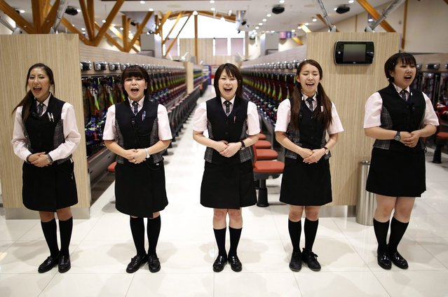 Dynam employees say a greeting message as they receive customer-care training ahead of the grand opening of the company's pachinko parlour in Fukaya, north of Tokyo July 29, 2014. (Photo by Issei Kato/Reuters)
