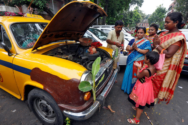 Family members of a taxi driver offer prayer in front of their taxi during the Vishwakarma Puja or the festival of the Hindu deity of architecture and machinery in Kolkata, India, September 17, 2017. (Photo by Rupak De Chowdhuri/Reuters)