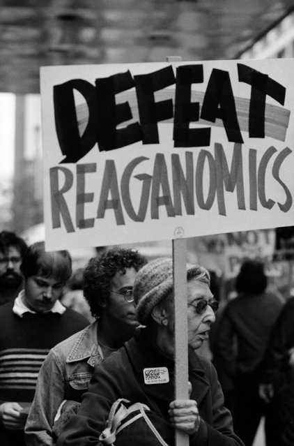"Woman demonstrator holds ""Defeat Reaganomics"" sign down the street from hotel in which President Reagan stayed in Chicago, September 3, 1981. Police kept the demonstrators one-half block from the President. (Photo by Jim Bourdier/AP Photo)"