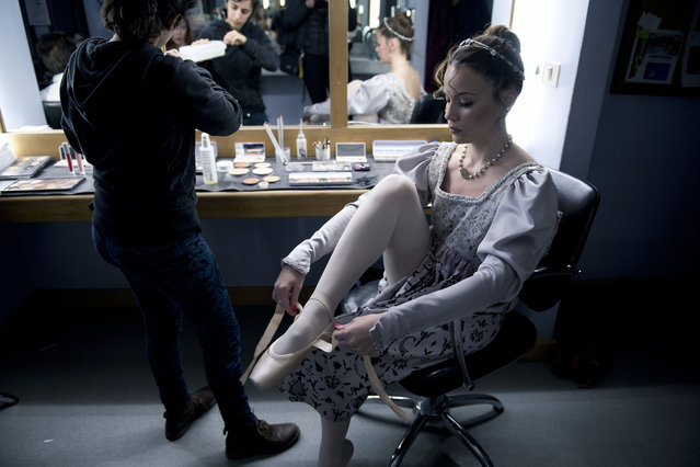 In this Friday, September 15, 2017 photo, a dancer puts her ballet shoes on before a dress rehearsal for Romeo and Juliet in Montevideo, Uruguay. About 70 professional dancers in the Uruguayan capital train under the eye of a man who wants to turn the ballet company of this small South American nation into one of the best in the world. (Photo by Matilde Campodonico/AP Photo)