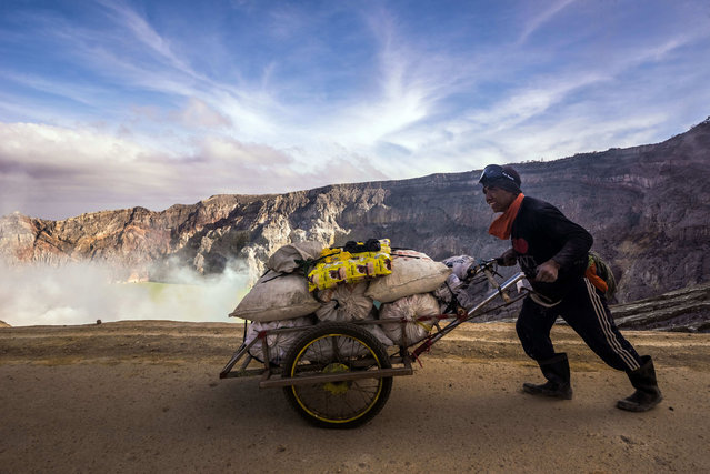 A miner with a full load of sulfur starts rolling down his trolley to the checkpoint – which is 3km downhill. It will take him about an hour. He still had to carry up the load to the rim, roughly 175 vertically up. Trolleys cost about 2 million Rupiah (150 USD). Not all of the miners can afford one. Most of the trolleys are coming from donations. (Photo by Claudio Sieber/Barcroft Images)