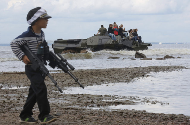 A boy walks with toy guns as people ride an APC during a military show at the Finnish Gulf coast in St.Petersburg, Russia, Saturday, September 5, 2015. (Photo by Dmitry Lovetsky/AP Photo)