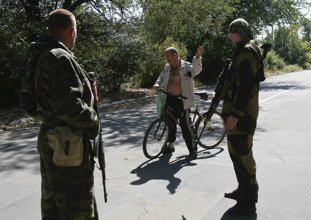 Pro-Russian separatists talk to a local resident at a check point on the outskirts of Donetsk September 6, 2014. (Photo by Maxim Shemetov/Reuters)