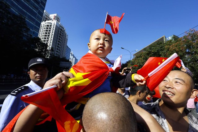 A child draped in a Chinese national flag sits on a man's shoulders during an anti-Japan protest near the Japanese Embassy in Beijing, on September 18, 2012. The 81st anniversary of a Japanese invasion brought a fresh wave of anti-Japan demonstrations in China, with thousands of protesters venting anger over the colonial past and a current dispute involving contested islands in the East China Sea. (Photo by Ng Han Guan/Associated Press)