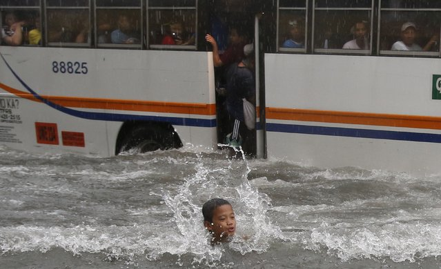 A boy plays at a flooded street in front of a passing bus as tropical storm Fung-Wong battered the Philippine capital Manila September 19, 2014. Heavy rain in the Philippine capital, Manila, caused flooding in many areas on Friday, shutting schools, government offices and financial markets as a tropical storm made landfall to the north. Thousands of residents in low-lying areas were moved to higher ground, officials said, as flood waters rose quickly after the equivalent of half a month's usual rain fell in six hours. (Photo by Erik De Castro/Reuters)