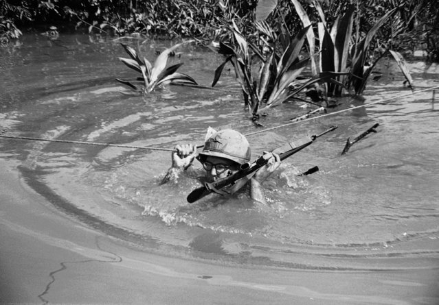 Trooper of the U.S. 1st division uses one hand to hang on to rope and the other to hold his M16 above the water as he is pulled across a stream in an area his unit was patrolling about 10 miles east of Saigon on July 15, 1968. (Photo by AP Photo)