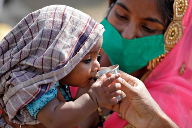 A child of a migrant worker drinks water as his mother holds him while waiting in a queue for transport to reach to a railway station to board a train to their home state of northern Uttar Pradesh, after a limited reopening of India's giant rail network following a nearly seven-week lockdown to slow the spreading of the coronavirus disease (COVID-19), in Ahmedabad, India, May 15, 2020. (Photo by Amit Dave/Reuters)