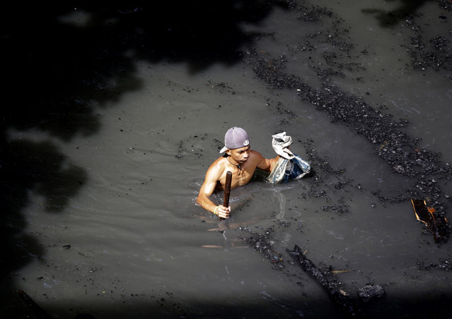 A resident wades through a polluted creek to sift through the debris Tuesday, September 16, 2014, a day after a fire razed more than 60 houses at an informal settlers' community at suburban Paranaque, south of Manila, Philippines. Village officials said no one was injured in the fire but rendered more than 700 people homeless. (Photo by Bullit Marquez/AP Photo)