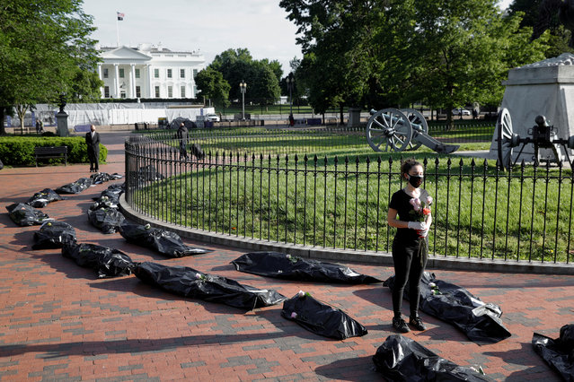 Margot Bloch stands beside a line of mock body bags while holding flowers during a funeral procession demonstration for the coronavirus disease (COVID-19) victims outside of the White House in Washington, U.S., May 20, 2020. (Photo by Tom Brenner/Reuters)