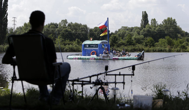 A man (L) fishes as Jan Kara, Jakub Bures, Jan Brand and Jan Holan pedal their boat, made with plastic bottles, on the Elbe river near Kostelec nad Labem July 15, 2014. (Photo by David W. Cerny/Reuters)