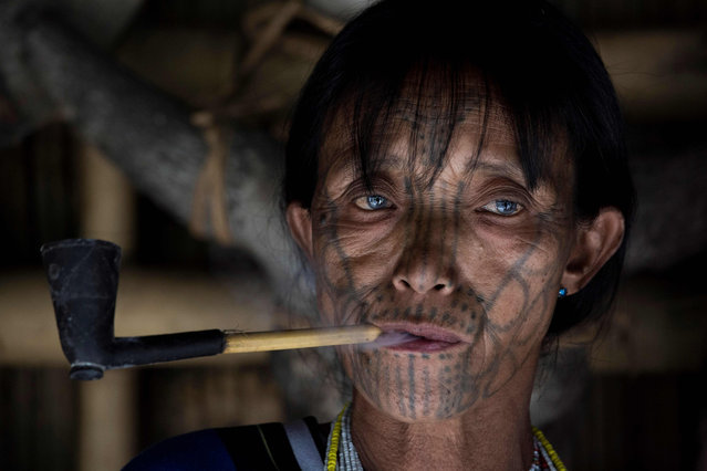 This photo taken on March 3, 2020 shows a tattooed Chin ethnic woman smoking at her house decorated with animal skulls in a village of Chin State, western Myanmar. (Photo by Sai Aung Main/AFP Photo)