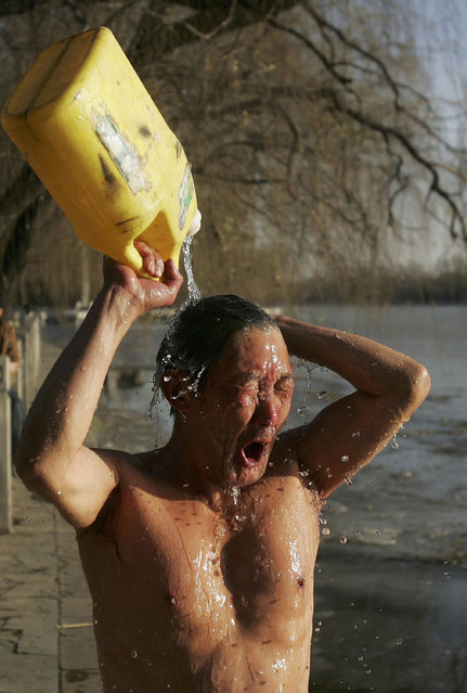A swimmer washes himself after winter swimming at Shichahai Lake on December 15, 2005 in Beijing, China. Winter swimming is a popular sport among Beijing residents. (Photo by China Photos)