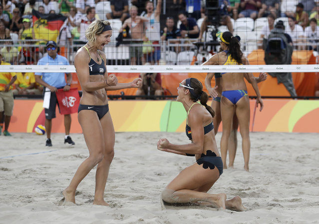 Germany's Laura Ludwig, left, and Kira Walkenhorst celebrate after beating Brazil during a women's beach volleyball semifinal match at the 2016 Summer Olympics in Rio de Janeiro, Brazil, Tuesday, August 16, 2016. (Photo by Marcio Jose Sanchez/AP Photo)