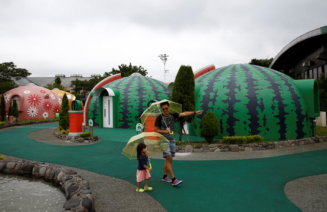 A family from Singapore takes a walk around quake-resistant dome houses at the Aso Farm Land resort in Aso, Japan on November 6, 2017. (Photo by Kim Kyung-Hoon/Reuters)