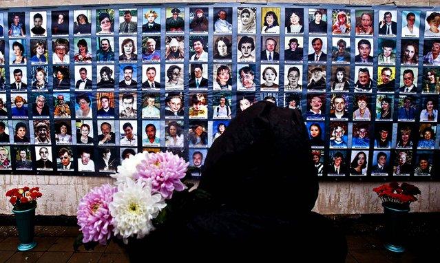 A woman with flowers stands in front of portraits of 130 victims who died in a hostage crisis at a Moscow theater 10 year ago, on  October 26, 2012. Chechen militants held 912 audience members for three days. (Photo by Misha Japaridze/Associated Press)