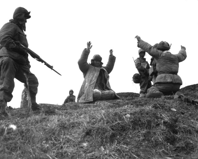 Men of the 1st Marine Division capture Chinese Communists during fighting on the central Korean front.  Hoengsong, March 2, 1951. (Photo by Pfc. C. T. Wehner, Marine Corps)